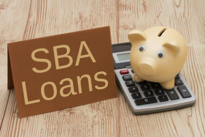 Getting a SBA Loan, A golden piggy bank, card and calculator on a wood background with text SBA Loans